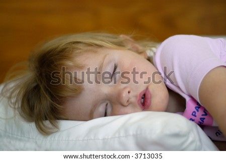 Little girl sleeping on bed with head on pillow
