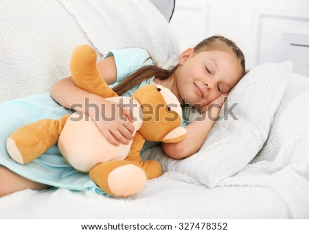 Little girl sleeping on sofa in room