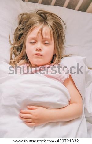 Little girl sleeps. Girl is sleeping.  Little girl dressed in pajamas asleep in bed in the children's room. - stock photo