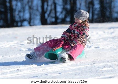 Little girl sliding with bob and falling in the snow.