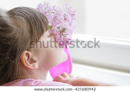 Little girl smelling a lilac in a vase on a windowsill - stock photo