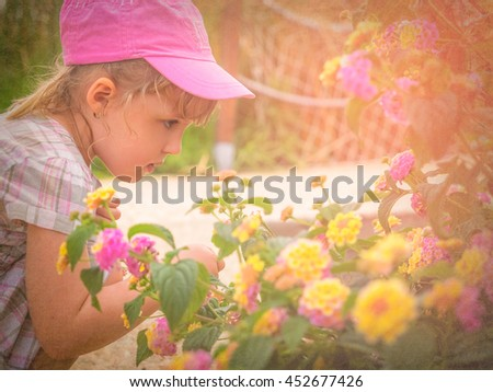Little girl smelling blossoming flowers in spring - stock photo