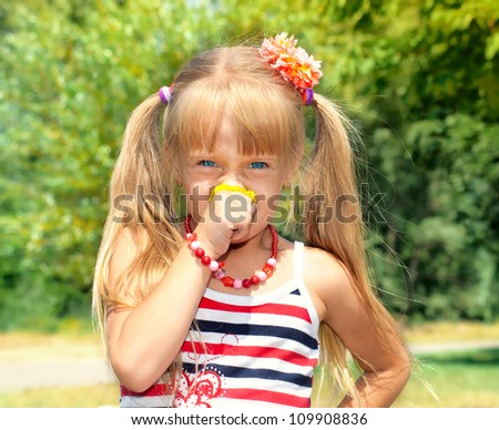 Little girl smelling yellow flower - stock photo