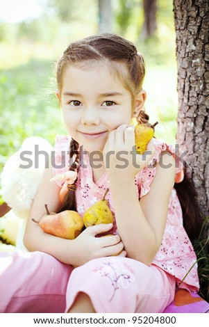 Little girl smiling and eating pears in the garden - stock photo