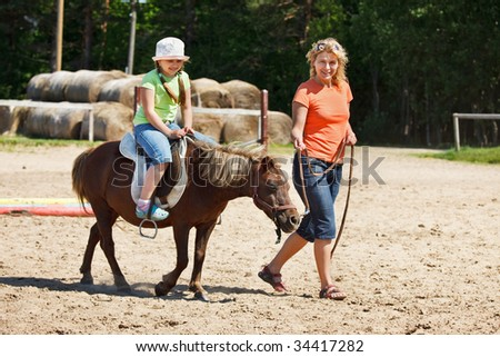 Little girl smiling and riding pony, woman leading pony by bridle - stock photo