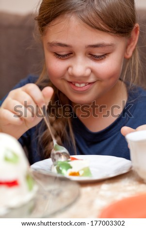 Little girl smiling, eating a piece of jelly cake - stock photo