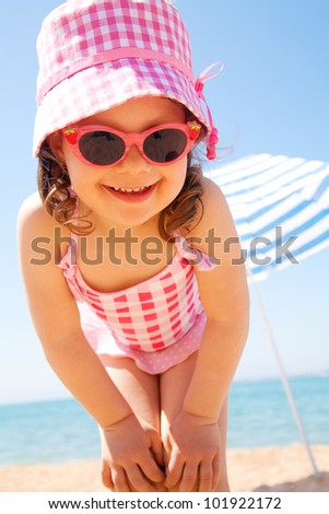 little girl smiling fun in the hot beach under an umbrella - stock photo