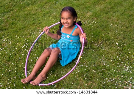 Little girl smiling in the grass playing with a hula hoop. Horizontally framed photograph - stock photo