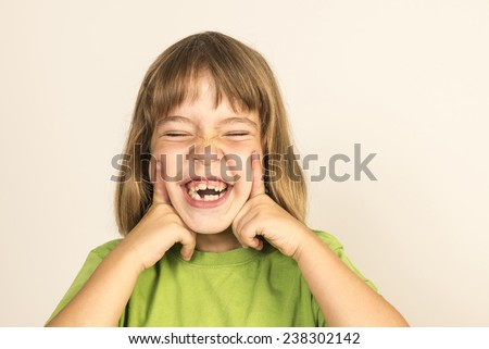 Little girl smiling with eyes closed isolated on white background  - stock photo