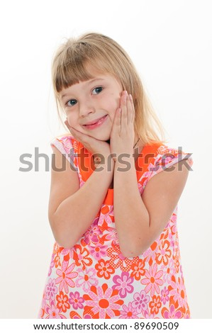 Little girl smiling with hands on her face
