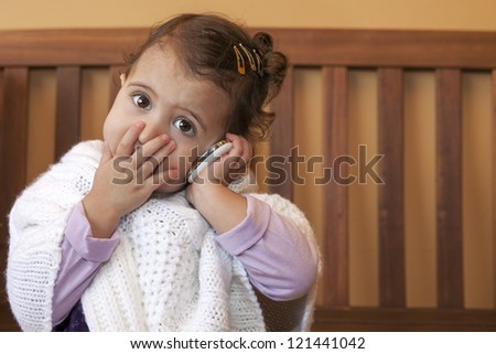 Little girl speak on the phone at home. looking worried - stock photo