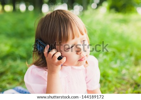 little girl speaks by phone