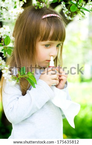 Little girl spraying medicine in nose, nose drops, nose spray. - stock photo