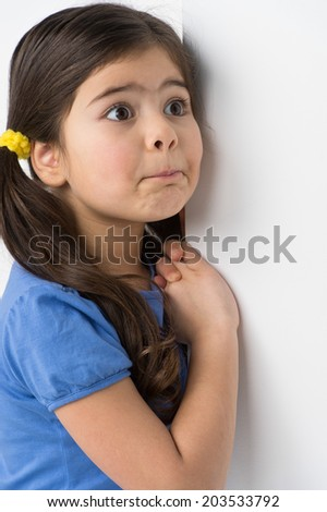 little girl standing and leaning against wall. nice girl making facial expression - stock photo