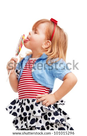 Little girl standing and licking big lollipop - stock photo