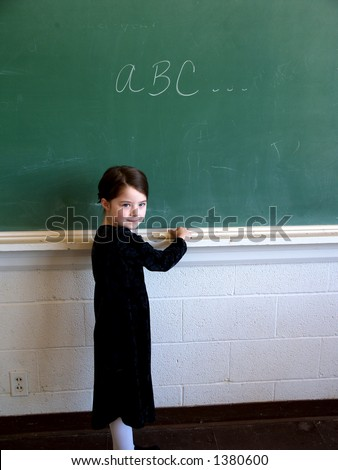 Little girl standing at chalk board