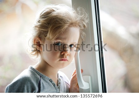 Little girl standing by the window - stock photo