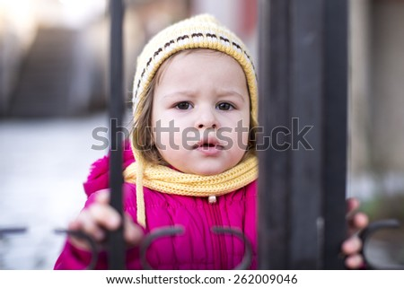 little girl standing in front of a gate in winter - stock photo