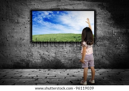 little girl standing in front of a large monitor on the background of gray walls - stock photo