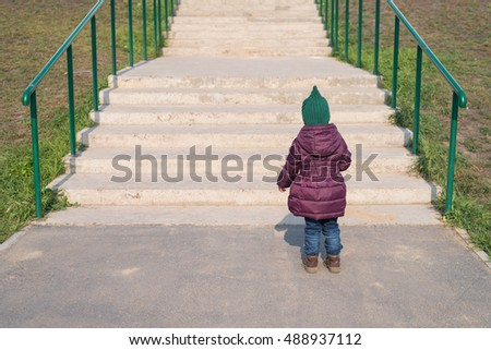 Little girl standing in front of the big staircase