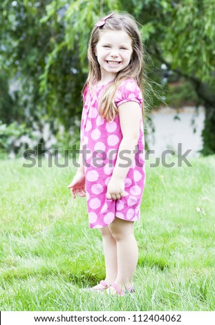 Little girl standing in the grass - stock photo