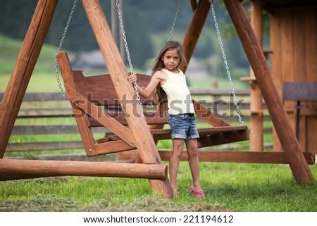 Little girl standing near swinging seat