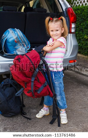 little girl standing near the car with backpacks - stock photo