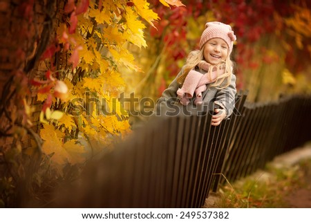 little girl standing near the fence in autumn