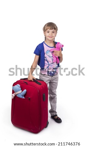 Little girl standing near the suitcase over white background - travel or vacation concept