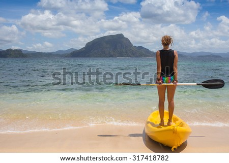 Little girl standing next to colorful yellow kayak