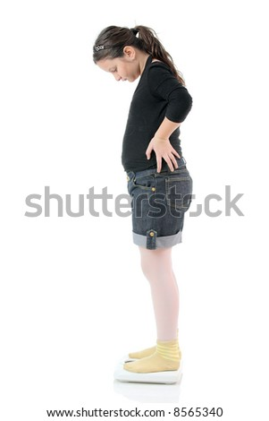 Little girl standing on a weight scale isolated on white background - stock photo