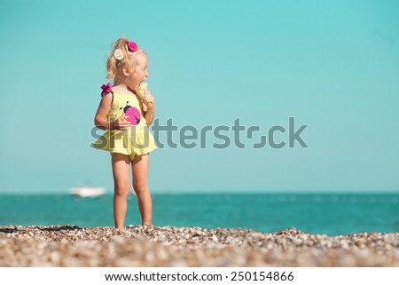 little girl standing on the beach and eating an ice-cream - stock photo