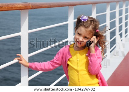 Little girl stands on board ship and talks by portable radio - stock photo