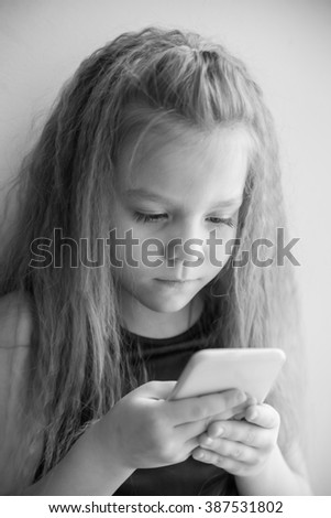 Little girl stares into the smartphone