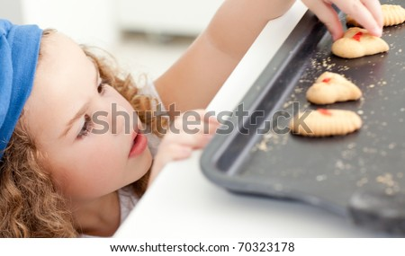 Little girl stealing cookies at home - stock photo