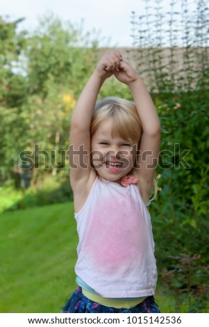 little girl stretching her arms in the garden