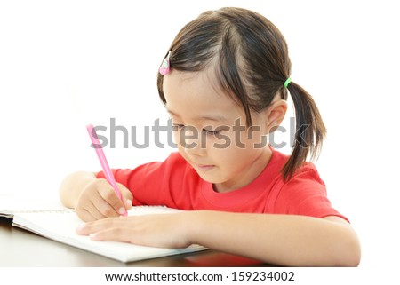 Little girl studying at the desk - stock photo