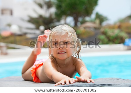 little girl sunbathing on a rock near pool