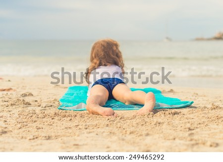 Little girl sunbathing on sand. Place for text. - stock photo