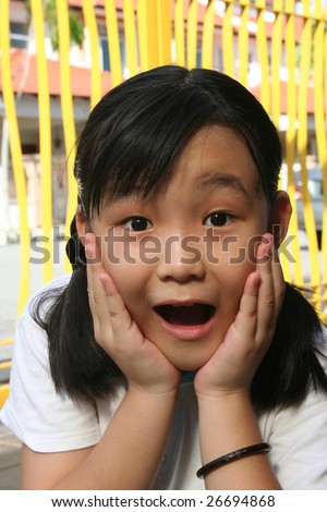 Little girl surprised and shocked with hands holding her face - stock photo