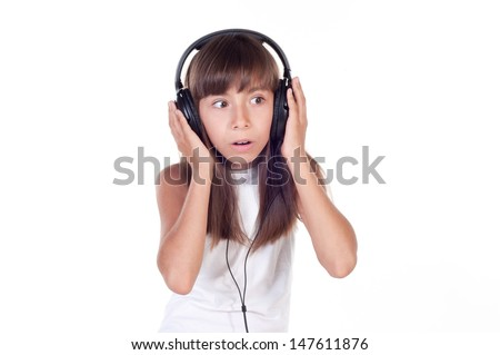 Little girl surprised with headphones on white background