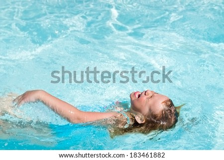 Little girl swimming in the pool with her eyes closed