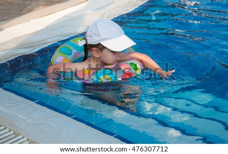 little girl swims in a swimming pool