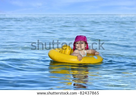 Little girl swims in an inflatable yellow float ring - stock photo