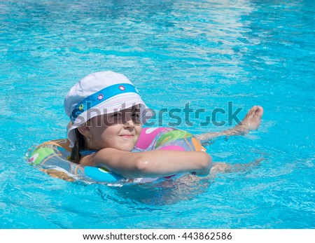 little girl swims in the pool on inflatable circle
