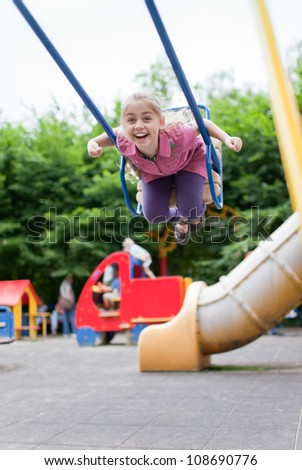 Little girl swinging on the playground at summer day - stock photo