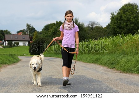 Little girl taking a dog for a walk outdoors in nature - stock photo