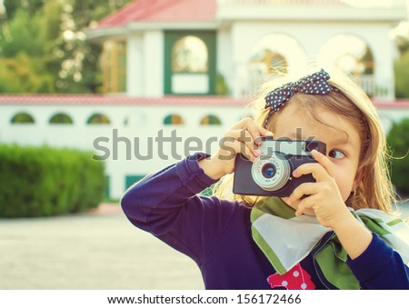 Little girl taking  picture using vintage film camera - stock photo