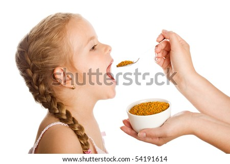 Little girl taking pollen granules with spoon - traditional remedies concept - stock photo