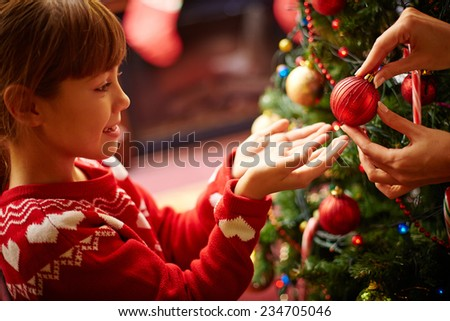 Little girl taking red decorative toy ball - stock photo